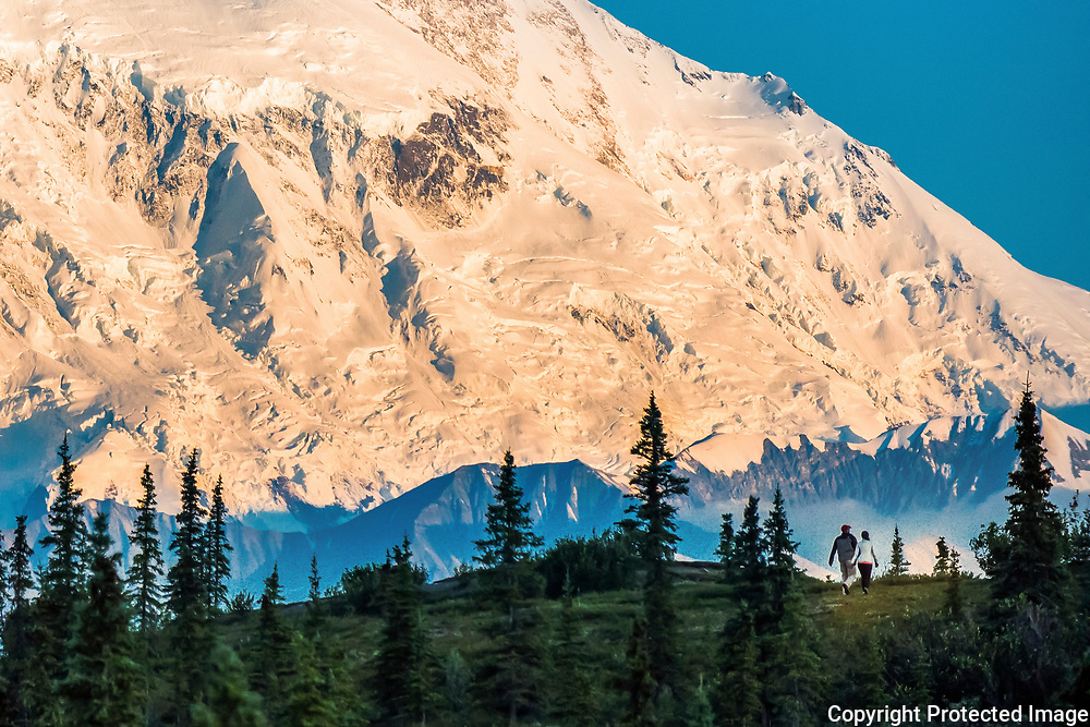 Hikers get a closer view of Mt. Denali as the sun sets near Wonder Lake Campground. Denali is the tallest mountain in North America at over 20,000 feet. When the sun sets it glows orange which creates what is known as an alpenglow.<br /> -2015