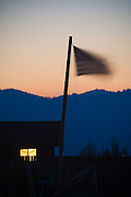 A window glows from a small ranch house flying the American flag in the outskirts of Victor, Idaho.