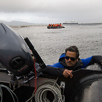 Adventure travel guide pushes raft ashore at Cape Horn, Tierra del Fuego, Chile.