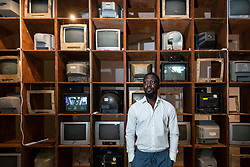 """© Licensed to London News Pictures. 21/10/2021. LONDON, UK. Artist Ibrahim Mahama poses with his large-scale analogue TV art installation made from e-waste in Ghana. Preview of """"Waste Age: What can design do?"""", an exhibition at the Design Museum to see what the design industry can do to tackle its environmental consequences around the globe.  The exhibition coincides with the upcoming UN Climate Change Conference of the Parties (COP26) taking place in Glasgow.  Photo credit: Stephen Chung/LNP"""
