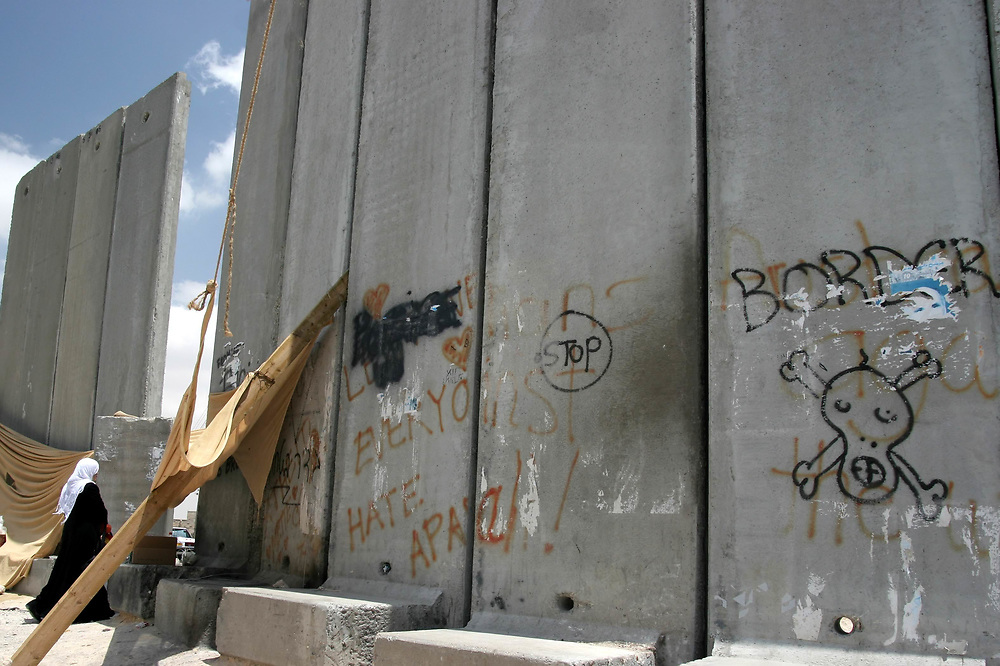 A Muslim woman walks through an opening in Israel's separation barrier in the East Jerusalem village of Abu-Dis on May 8, 2006.<br /> In June 2002, the government of Israel decided to erect a physical barrier to separate Israel and the West Bank in order to prevent the uncontrolled entry of Palestinians into Israel . In most areas, the barrier is comprised of an electronic fence with dirt paths, barbed-wire fences, and trenches on both sides, at an average width of 60 meters. In some areas, a wall six to eight meters high has been erected in place of the barrier system. <br /> Of all Israel's separation barriers, it is the most hotly controversial - between Israelis and Palestinians, internationally, and also inside the Israeli society itself. The controversy stems mainly from the government's decision not to stick to Israel's 1949 Armistice lines (Green Line) but rather build the barrier within the West Bank - in some stretches, deeply within, dividing villages and neighborhoods.<br /> Opponents of the project say that this proves its purpose is not to stop suicide bombers, which would been equally served by a fence along the Green Line, but by the intention to effectively annex parts of the West Bank, especially those where Israeli settlements have been created, as well as water sources - and define the future borders with Palestine unilaterally and ahead of negotiations.<br /> Supporters assert that the barrier is a necessary tool protecting Israeli civilians from Palestinian terrorism, including suicide bombing attacks that increased significantly during the al-Aqsa Intifada. It has helped to significantly reduce incidents of terrorism from 2002 to 2005; its supporters assert that the onus is on the Palestinian Authority to fight terrorism.