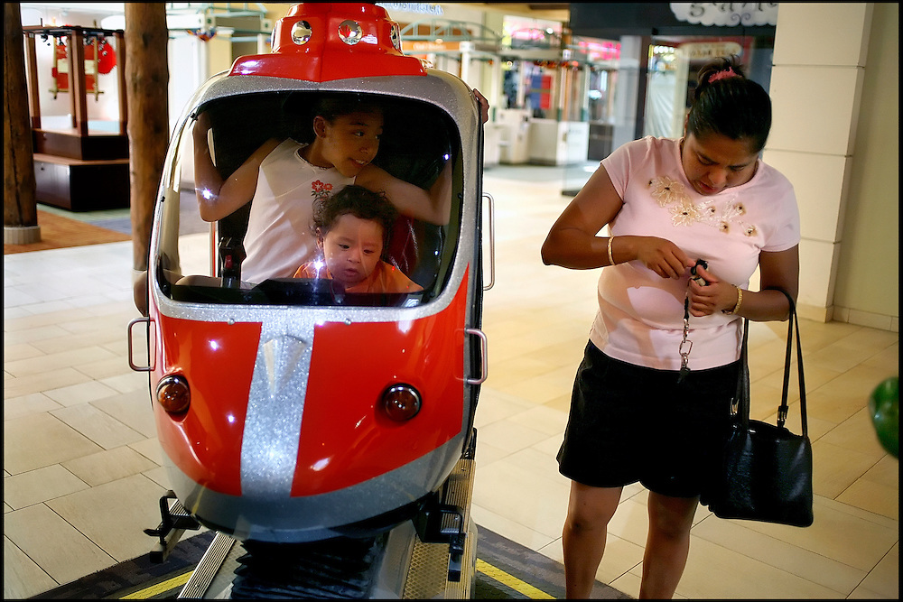 Lupita Hernandez digs for spare change so her children can enjoy a ride at the mall.  Before the family moved into a new house, she often took the children to the mall in the summer as their apartment had no air conditioning.