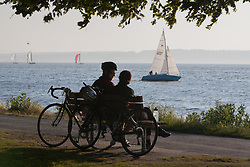 North America, United States, Washington, Seattle, couple with bicycles at Golden Gardens Park by Ellott Bay