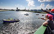 De Arctic Sunrise wordt welkom geheten als het Amsterdam binnenvaart. In IJmuiden is de Arctic Sunrise, het schip van milieuorganisatie Greenpeace dat een jaar door Rusland in beslag is genomen, aangekomen. De voormalige ijsbreker wordt in Amsterdam uit het water gehaald en opgeknapt omdat het gehavend is geraakt toen het aan de ankers lag. De boot van de milieuorganisatie is september 2013 door de Russen geënterd en de bemanningsleden vastgezet op verdenking van piraterij. Greenpeace voerde actie bij een boorplatform in de Barentszzee. Als het schip weer is gerepareerd, wil de milieubeweging weer campagnes houden met de Artic Sunrise.<br /> <br /> In IJmuiden, the Arctic Sunrise, the Greenpeace ship that a year ago is seized by Russia, arrived. The former ice breaker is removed from the water in Amsterdam and refurbished since it was damaged when it was up to the anchors. The boat of the environmental organization is boarded in September 2013 by the Russians and the crew put down on suspicion of piracy. Greenpeace campaigned on a drilling platform in the Barents Sea. If the ship is repaired, the environmental movement wants to use the Arctic Sunrise again for campaigning.