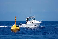 Sport fishing boat trolling around OTEC FAD (Fish Aggregation Device) in search of a big game, off Kona Coast, Big Island, Hawaii, Pacific Ocean.