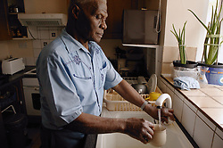 Elderly man standing at a sink filling a mug of water,
