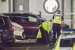 © Licensed to London News Pictures. 10/08/2017. Salford, UK. Police examine a maroon coloured car in a car park at the rear of the Ibis Hotel in Salford Quays where a young boy was killed in a collision with a car earlier this evening (Thursday 10th August 2017) . Photo credit: Joel Goodman/LNP