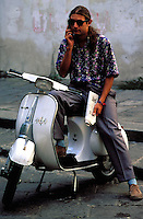 Italian man with mobile telephone and Vespa, lorence , Tuscany, Italy