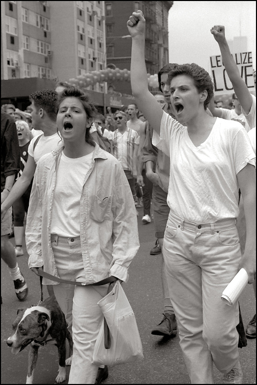 """Nancy Brooks Brody and Zoe Leonard of ACT UP NY, on June 24, 1989, the 20th anniversary of the Stonewall riots, participating in a renegade march up 6th avenue to Central Park. Themed, """"In The Tradition"""", this march followed the same route as the original march 20 years ago and was designed as a rebuke to the corporatization of the gay pride parade."""
