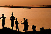 Girls take a break from washing clothers and dishes in the Niger river at sunset in the W. African village of Kouakourou, Mali. Material World Project.