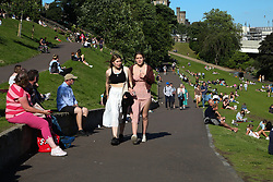 © Licensed to London News Pictures. 14/07/2021. Edinburgh, Scotland, UK. People enjoy a hot evening in Princes Street Gardens in Edinburgh as warm weather continues in Scotland. According to the Met Office, a high of 22 degrees celsius is forecast for the rest of the week. Scotland's first minister, Nicola Sturgeon has said that Scotland will move to a 'modified' form of level 0 on 19 July and 15 adults from 15 households can meet outdoors in a private garden or public place. Photo credit: Dinendra Haria/LNP
