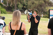 A male protester speaks using a megaphone to a small group of anti-lockdown protesters on the St Kilda beach foreshore. After over 3 months of covid-19 lockdowns in Melbourne the easing of restrictions, allowed a small group of protesters to gather on St Kilda beach to protest police handing of demonstrations during the lock down. (Photo by Michael Currie/Speed Media)