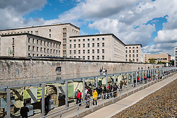 View of tourists visiting outdoor museum at Topography of Terror former Gestapo headquarters in Berlin Germany