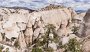 """Hoodoos panorama. See fantastic hoodoos and a great slot canyon in Kasha-Katuwe Tent Rocks National Monument, in New Mexico, USA. Hike the easy Cave Loop Trail plus Slot Canyon Trail side trip (3 miles round trip), 40 miles southwest of Santa Fe, on the Pajarito Plateau. Distinctive cone-shaped caprocks protect soft pumice and tuff beneath. Geologically, the Tent Rocks are made of Peralta Tuff, formed from volcanic ash, pumice, and pyroclastic debris deposited over 1000 feet thick from the Jemez Volcanic Field, 7 million years ago. Kasha-Katuwe means """"white cliffs"""" in the Pueblo language Keresan. This panorama was stitched from 6 overlapping photos."""