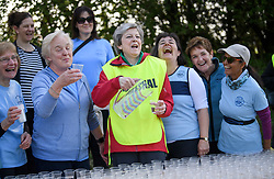 © Licensed to London News Pictures. 19/04/2019. Maidenhead, UK. Prime Minister THERESA MAY  helps out at at a drinks stand at the Maidenhead Easter 10 run in her constituency of Maidenhead in Berkshire. Parliament currently on Easter recess after an extension to Article 50 was granted by the EU. Photo credit: Ben Cawthra/LNP