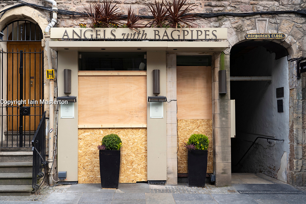 Edinburgh, Scotland, UK. 18 April 2020. Views of empty streets and members of the public outside on another Saturday during the coronavirus lockdown in Edinburgh. Angels with Bagpipes shop on Royal Mile  closed and boarded up. Iain Masterton/Alamy Live News