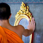 Young robed monk and mirror in Wat Pho temple (Bangkok, Thailand - Oct. 2008) (Image ID: 081012-1611042a)
