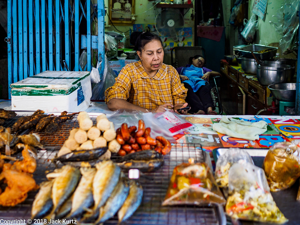 17 DECEMBER 2018 - BANGKOK, THAILAND: A food vender in her shop in a working class neighborhood about one kilometer from Siam Paragon, an exclusive mall in central Bangkok. According to Credit Suisse Global Wealth Databook 2018, which surveyed 40 countries, Thailand has the highest rate of income inequality in the world. In 2016, Thailand was third, behind Russia and India. In 2016, the 1% richest Thais (about 500,000 people) owned 58.0% of the Thailand's wealth. In 2018, they controlled 66.9%. In Russia, those numbers went from 78% in 2016, down to 57.1% in 2018. The Thai government disagreed with the report and said the report didn't take government anti-poverty programs into account and that Thailand was held to an unfair standard because most of the other countries in the report are developed countries in the Organisation for Economic Co-operation and Development.      PHOTO BY JACK KURTZ