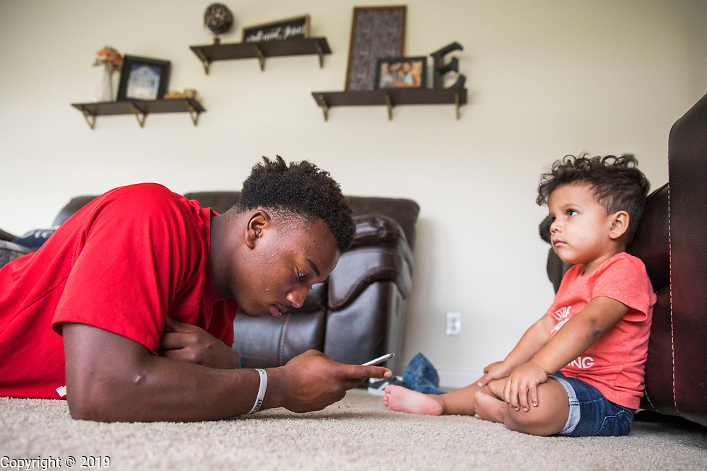 Edgewood football player Levon Bellamy reads his phone at home while his cousin Malachi Escobedo, right, watches TV, Wednesday, September 19, 2018 in Ellettsville, Ind.