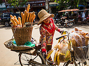 01 JUNE 2016 - SIEM REAP, CAMBODIA: A baguette vendor in the Siem Reap market. There are growing concerns that spot food shortages, especially of fish, the Cambodians main source of protein, could become worse if the coming rainy season doesn't bring relief from the drought that has gripped Cambodia for the last two years.          PHOTO BY JACK KURTZ