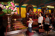"People praying inside one of the main buildings at Yonghe Temple, also known as the ""Palace of Peace and Harmony Lama Temple"", the ""Yonghe Lamasery"", or - popularly - the ""Lama Temple"" is a temple and monastery of the Geluk School of Tibetan Buddhism located in the northeastern part of Beijing, China. It is one of the largest and most important Tibetan Buddhist monasteries in the world. The building and the artworks of the temple is a combination of Han Chinese and Tibetan styles."