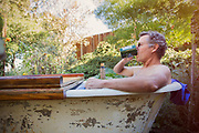 Senior adult man drinking coffee in bathtub in backyard.