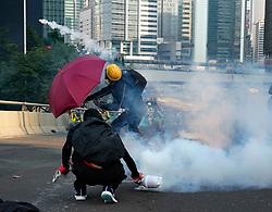 Hong Kong. 1 October 2019. After a peaceful march through Hong Kong Island by an estimated 100,000 pro democracy supporters, violent flared up at Tamar, Admiralty and moved through Wanchai district. Police used teargas and baton rounds and water cannon. Hard core group lit fires, threw bricks and Molotov cocktails at police. Violence continues into evening. Protestors return teargas canister. Iain Masterton/Alamy Live News.