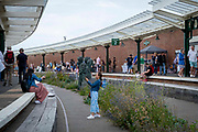 People shopping at the Sunday market on Folkestone Harbour Arm on the 25th of July 2021 in Folkestone, United Kingdom. The harbour company have restored the old railway station into an open air walkway with overhanging glass canopies. There is now a bustling market there every Sunday full of boutique stalls from local artists and designers.
