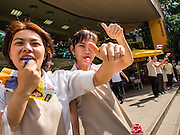 29 NOVEMBER 2013 - BANGKOK, THAILAND: Women who work in a bakery frequented by foreign tourists cheer anti-government protestors on Witthayu Road (also known as Wireless Rd). Although the government has a popular mandate, most of its supporters are from the rural northeast part of Thailand. Most members of Bangkok's middle class oppose the government. Several thousand Thai anti-government protestors marched on the US Embassy in Bangkok. They blew whistles and asked the US to honor their efforts to unseat the elected government of Yingluck Shinawatra. The anti-government protestors marched through several parts of Bangkok Friday paralyzing traffic but no clashes were reported, even after a group protestors tried to occupy Army headquarters.       PHOTO BY JACK KURTZ