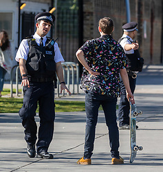 © Licensed to London News Pictures. 05/04/2020. London, UK. Police question a skateboarder in Normand Park, Fulham as members of the public come out to exercise as temperatures reach over 21c this weekend. The Government has urged the public not to leave home during the fine weather to help save lives as the Coronavirus crisis continues. Photo credit: Alex Lentati/LNP