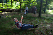 A 15 year-old boy blurs across woodland during a home-made zip wire ride on private land in Somerset. The old but sprightly and active gentleman keeps his legs straight to avoid scraping them along the woodland floor and stopping him before the end of the short ride. In the background are members of his family of varying ages, encouraging and laughing as he sweeps past on this bright summer afternoon.