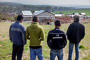 Rudolf (52, right), Michal (22, 2nd right), Rudo (25, 3rd right) and a friend of the family looking from a little hill to the construction side of the familie's selfconstructed buildings in Rankovce. After one year of contruction (04/2014) the familie's are already able to life in the houses. They joined a micro loan program in Rankovce.