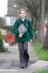 Schoolgirl with a science book under her arm walking to school in Banstead Surrey UK