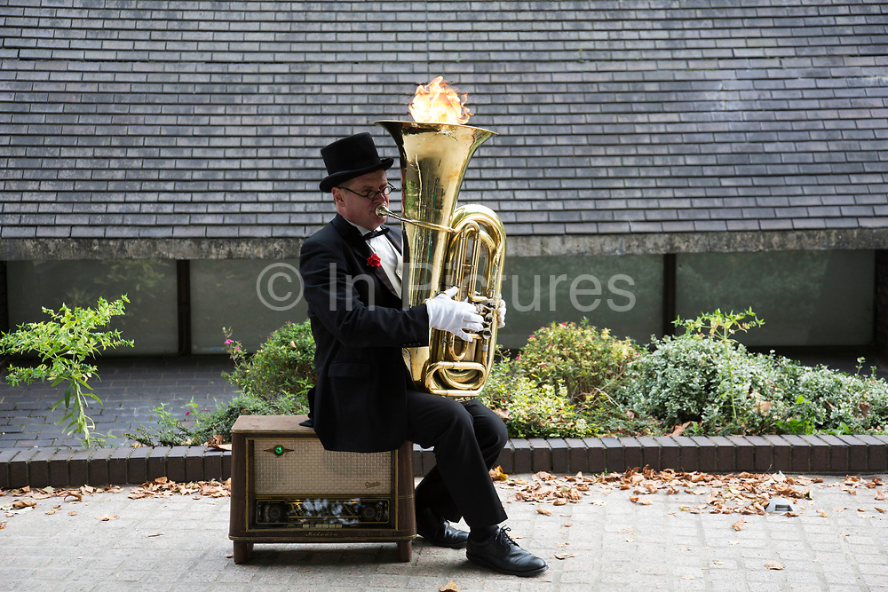 Christopher Werkowicz, a street entertainer and busker playing a tuba which shoots out fire. Using a switch on the side of the instrument, a small amount of gas is released and flames appear. The South Bank is a significant arts and entertainment district, and home to an endless list of activities for Londoners, visitors and tourists alike.