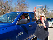 "26 APRIL 2020 - JEWELL, IOWA: PEG THOMPSON, wearing a mask because of the COVID-19 pandemic, signals that people in a car want four ""grab and go"" roast pork dinners in Jewell during a fund raiser Sunday. Jewell, a small community in central Iowa, became a food desert when the only grocery store in town closed in 2019. It served four communities within a 20 mile radius of Jewell. Some of the town's residents are trying to reopen the store, they are selling shares to form a co-op, and they hold regular fund raisers. Sunday, they served 550 ""grab and go"" pork roast dinners. They charged a free will donation for the dinners. Despite the state wide restriction on large gatherings because of the COVID-19 pandemic, the event drew hundreds of people, who stayed in their cars while volunteers wearing masks collected money and brought food out to them. Organizers say they've raised about $180,000 of their $225,000 goal and they hope to open the new grocery store before summer.           PHOTO BY JACK KURTZ"