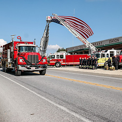 vFellow firefighters salute the funeral procession for a fallen volunteer firefighter in Lancaster County.