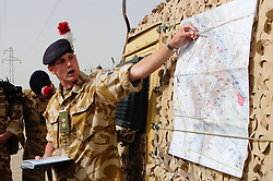 ABritish Army Lieutenant  from the  gives an open air briefing to his men, using a map fastened to the side of a Land Rover  before they set out on a Patrol in Basra, Iraq during Op Telic 2005