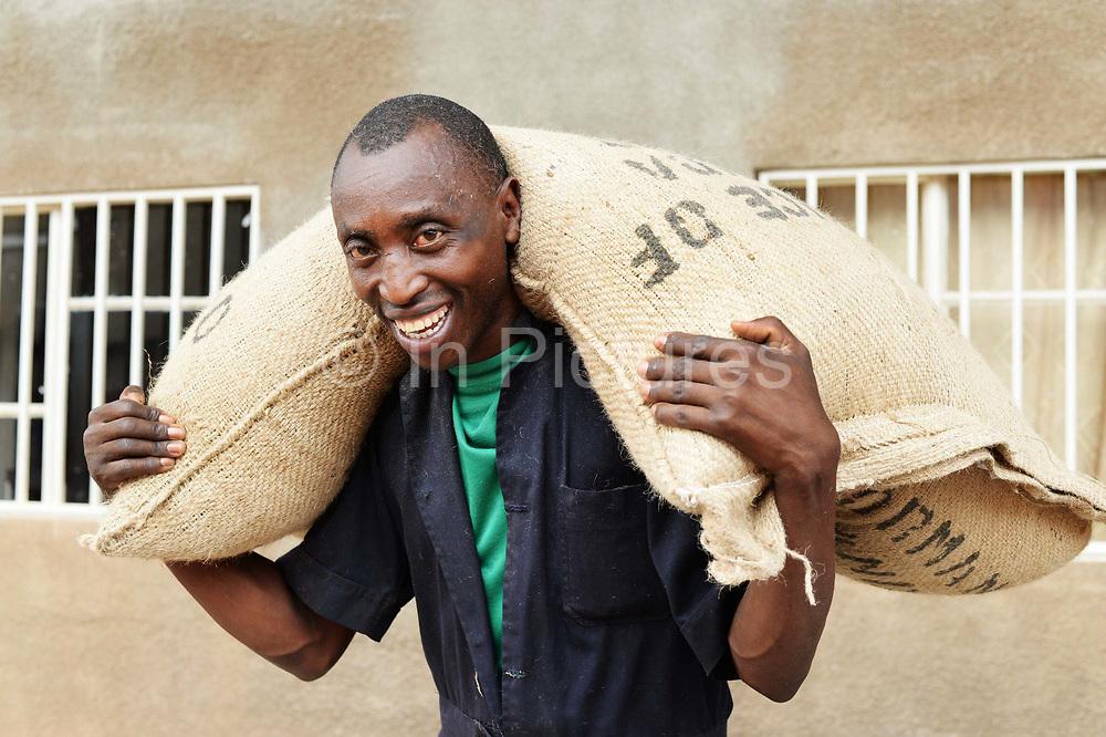 Rwanda 2014 Kigali. Worker carring sack of coffee beans for roasting