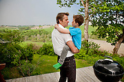 The Glad Ostensen family in Gjerdrum, Norway. Anders Ostensen, 48, and his son, Amund, 8, on the back porch of their farmhouse as a windy thunderstorm approaches. Model-Released.