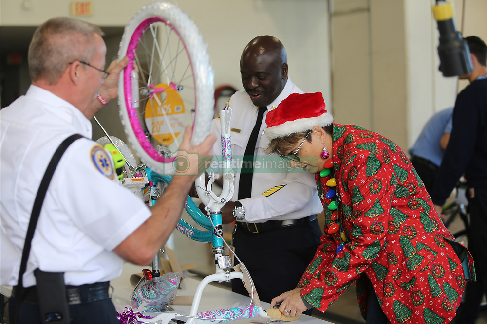 December 18, 2018 - Orlando, FL, USA - From left, Lt. Geoff Corah, Chief Roderick Williams, and Commissioner Patty Sheehan assemble a bicycle. Orlando firefighters helped assemble nearly 90 bikes that will be donated to children in the Reeves Terrace neighborhood, on Tuesday, December 18, 2018. The ''bike build'' event was part of the 17th annual Wheels for Kids program Sheehan started in 2002. (Credit Image: © Ricardo Ramirez Buxeda/Orlando Sentinel/TNS via ZUMA Wire)