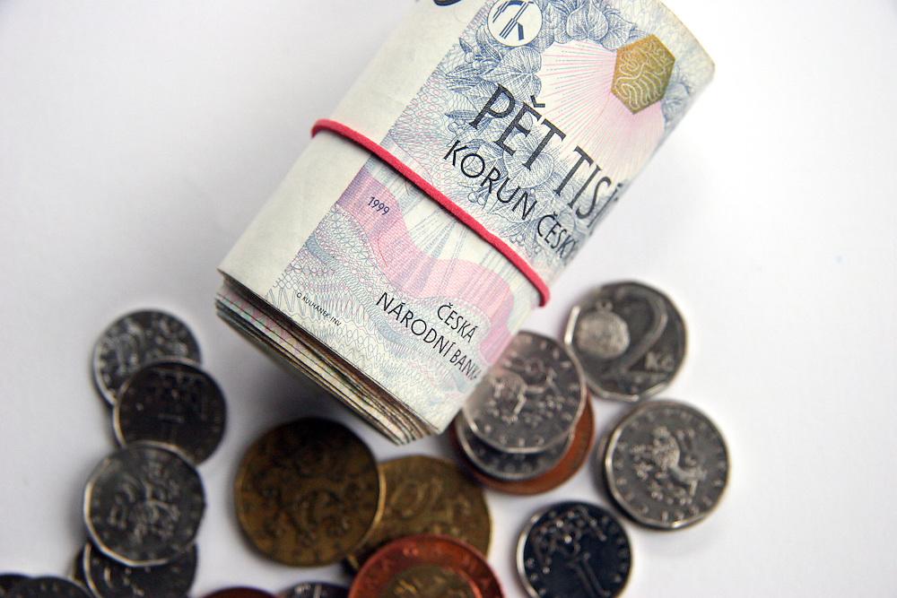 Lysa nad Labem/Tschechische Republik, Tschechien, CZE, 19.01.07: Geldbündel mit Gummiband aus tschechischen Banknoten (Kronen) und tschechisches Münzgeld - außen ein 5000 Kronen Schein.<br /> <br /> Lysa nad Labem/Czech Republic, CZE, 19.01.07: Rouleau made out of Czech bank notes - on the outside a 5000 crowns note. In front Czech coin money.