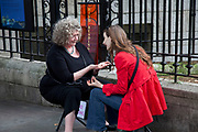 Woman giving a hand reading to another woman on the street near to Leicester Square. The woman in red as speaking desperately to the reader.