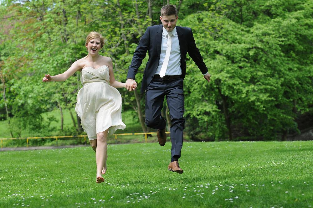 Braut und Bräutigam hüpfen bei guter Laune glücklich über eine Wiese |     young couple on wedding day jumping over a meadow |