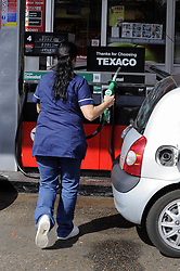 © Licensed to London News Pictures. 29/03/2012. Orpington, UK. A woman filling a car with petrol at a petrol station in Orpington, South London on March 29, 2012. Photo credit : Grant Falvey/LNP