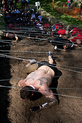© Licensed to London News Pictures. 12/05/2012. Kettering, UK. Tough Mudder competitors crawling up a muddy hill underneath barbed wire. Thousands of people took part in Tough Mudder today (12/05) in the grounds of Boughton House, Northamptonshire. The 12 mile course which was designed by British special forces soldiers, consisted of 25 extreme obstacles including water, mud, electrocution, and high walls. The challenge is designed to test teamwork abilities as well as physical strength and stamina . Photo credit : James Gourley/LNP
