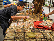 08 JANUARY 2015 - BANGKOK, THAILAND:  A man looks at amulets in a street side stall. Hundreds of vendors sell amulet and Buddhist religious paraphernalia to people in the Amulet Market, an area north of the Grand Palace near Wat Maharat in Bangkok.            PHOTO BY JACK KURTZ