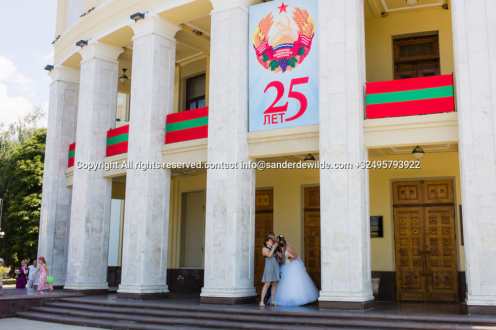 20150829  Moldova, Transnistria,Pridnestrovian Moldavian Republic (PMR) Tiraspol. A billboard celebrating the 25th year of existence of Transnistria and banners in the Transnistrian national colors hanging from the National Theatre, while a newly wed couple looks at their pictures with the photographer.