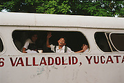 School boy waving from bus with the words in large print on the side of bus VALLADOLID, YUCAT