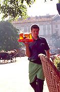 Waiter age 25 bringing drinks to table at sidewalk cafe.  Krakow Poland