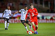 Wales midfielder Lee Evans hold off Trinidad and Tobago midfielder Ataullah Guerra during the Friendly European Championship warm up match between Wales and Trinidad and Tobago at the Racecourse Ground, Wrexham, United Kingdom on 20 March 2019.